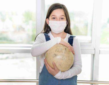 Mädchen mit Mundschutz hält einen Globus in den Händen