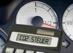 Taschenrechner mit den Worten CO2 Steuer vor dem Armaturenbrett eines Pkws