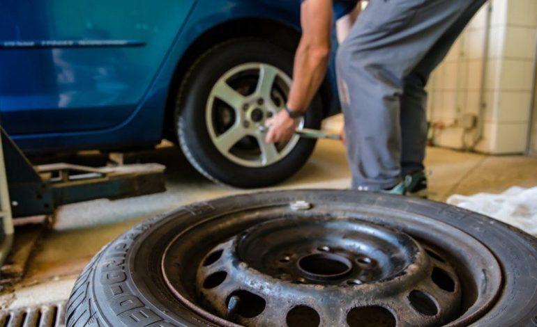 Ein Mann löst die Radmuttern am Auto. Im Vordergrund liegt ein zweiter Reifen zum Wechseln