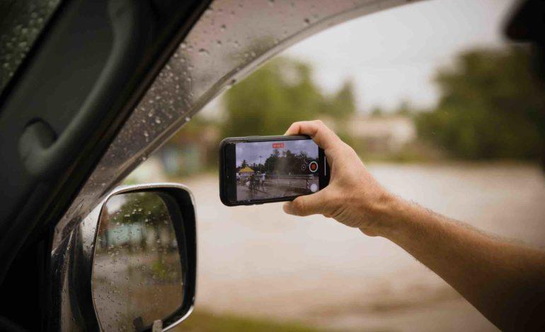 Ein Mann hält sein Smartphone zum Autofenster hinaus, um etwas zu filmen.