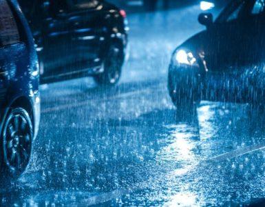 Autos fahren auf nasser Straße mit geringem Abstand. Die Autos fahren mit Licht, es ist dunkel.