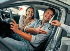 Ein Fahrer und eine Beifahrerin sitzen in einem neuen Auto. Dem Fahrer wird der Autoschlüssel überreicht.
