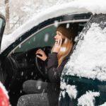 Frau in Winterkleidung sitzt bei offener Tür auf dem Fahrersitz eines Autos und telefoniert. Das Auto ist mit Schnee bedeckt und es schneit.