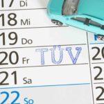 Auf einem Kalender ist ein TÜV Termin notiert. Daneben steht ein türkisfarbenes Spielzeugauto.