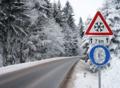 Straße durch einen verschneiten Wald. Verkehrsschild am Rand mit Schneeketten Symbol unter einem Warnschild für Schneefall für die nächsten 7 km