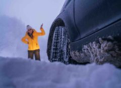 Auto im Schnee im Vordergrund, Fokus von unten auf Vorderreifen, Schnee hängt am Unterboden. Frau in Winterbekleidung im Hintergrund hebt ratlos eine Hand.