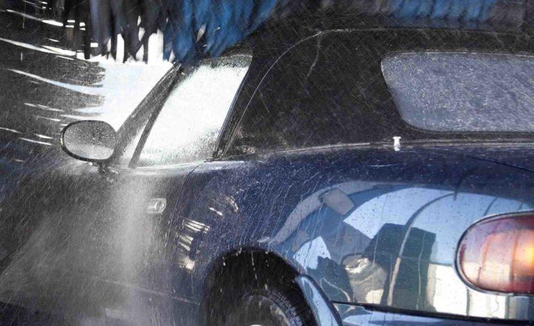 Blaues Auto in der Waschanlage mit blauen Bürsten.