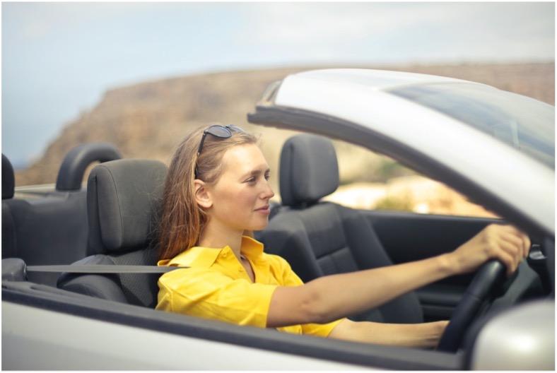 Frau mit gelber Kurzarm-Bluse und Sonnenbrille in den Haaren sitzt am Steuer eines offenen Cabrios.
