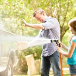 Vater und Tochter bei der Autowäsche. Tochter spritzt Wasser auf das Auto mit einem Gartenschlauch.