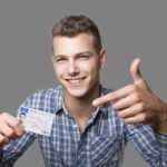 Lächelnder junger Mann hält seinen Führerschein hoch und zeigt darauf.