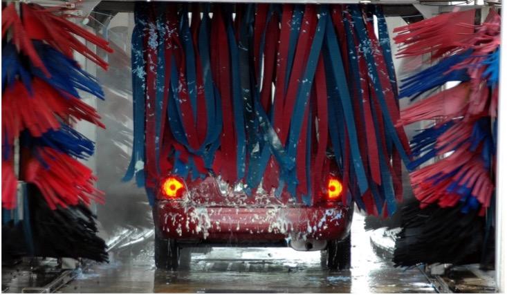Rotes Auto mit leuchtenden Rücklichtern zwischen den Bürsten der laufenden Waschanlage.