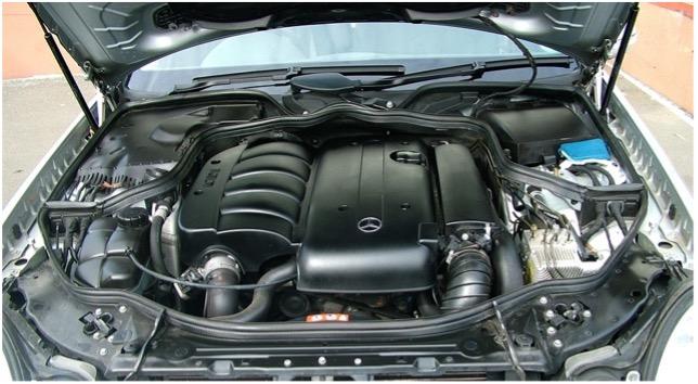 Motorraum eines Mercedes-Fahrzeugs unter geöffneter Motorhaube.