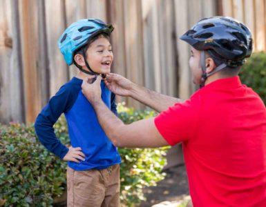 Mann mit Fahrradhelm und rotem Shirt kniet vor kleinem Jungen mit blauem Shirt und setzt ihm den Helm auf.