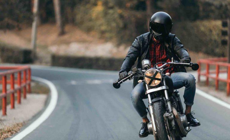 Motorradfahrer mit schwarzem Helm, Lederjacke und Jeans fährt auf einer Straße auf die Kamera zu.