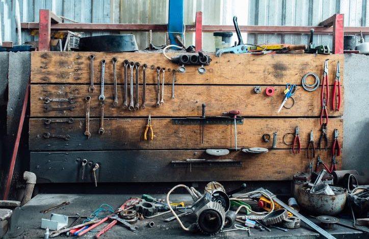 Verschiedene Werkzeuge liegen durcheinander in der Werkstatt der Garage. Alte Schraubenschlüssel hängen an der Holzwand darüber.