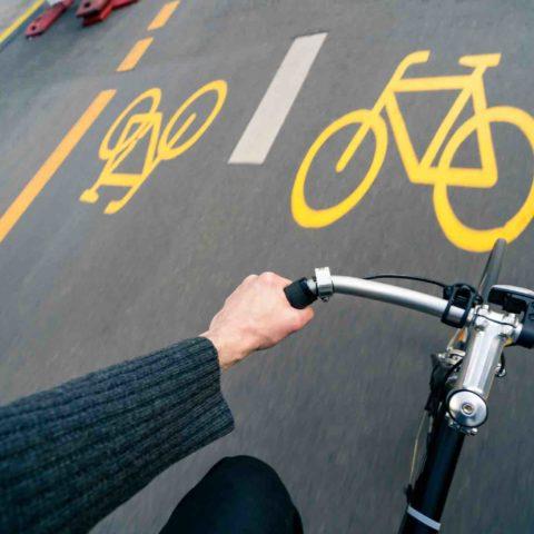 Sicht von oben auf den Lenker eines Fahrrads mit der linken Hand des Fahrers. Im Hintergrund gelbe Markierung von Pop-up-Radwegen.