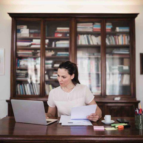 Frau mit Pferdeschwanz sitzt an einem Schreibtisch mit Laptop, Papierunterlagen, Kaffeetasse und Stiften. Im Hintergrund ist eine große Vitrine mit Büchern und Unterlagen.