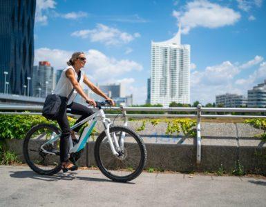 Frau mit Umhängetasche fährt auf einem E-Bike. Hochhäuser und blauer Himmel im Hintergrund.