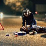 Frau wendet am Abend Erste Hilfe bei einem Mann an, der auf der Straße liegt. Daneben liegen der Verbandskasten und ein Warndreieck. Im Hintergrund sind Scheinwerfer zu sehen.