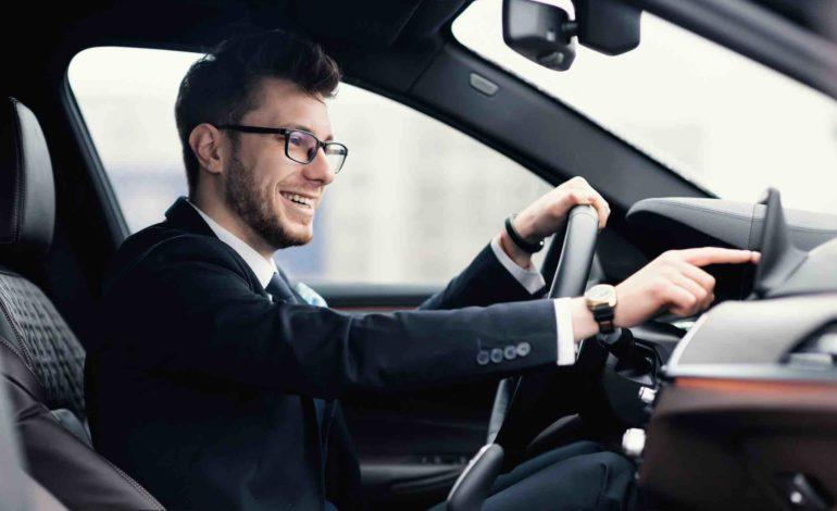 Mann mit Brille und Anzug im Auto mit einer Hand am Leckrad und einer Hand am Touchscreen im Armeturenbrett.