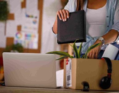 Frau packt Arbeitsunterlagen, Kopfhörer und eine Pflanze in einen Karton. Daneben steht ein aufgeklappter Laptop.
