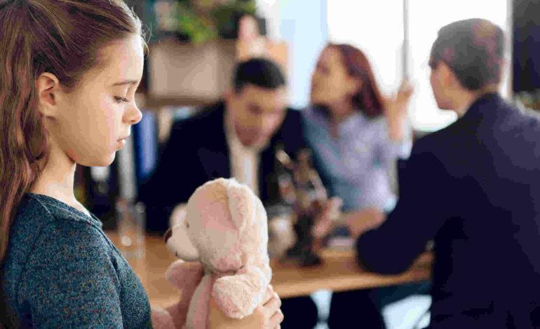 Mädchen mit Teddybär im Vordergrund. Dahinter Mutter und Vater in Diskussion mit Anwalt.