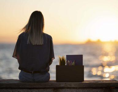 Junge Frau sitzt mit dem Rücken zur Kamera auf einer Mauer. Neben ihr steht eine Box mit Unterlagen, Schreibutensilien und einer Pflanze. Im Hintergrund ist ein Sonnenuntergang über dem Meer zu sehen.