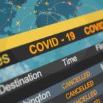 Bunte Anzeigetafel am Flughafen. Angezeigt werden stornierte Flüge aufgrund von COVID-19