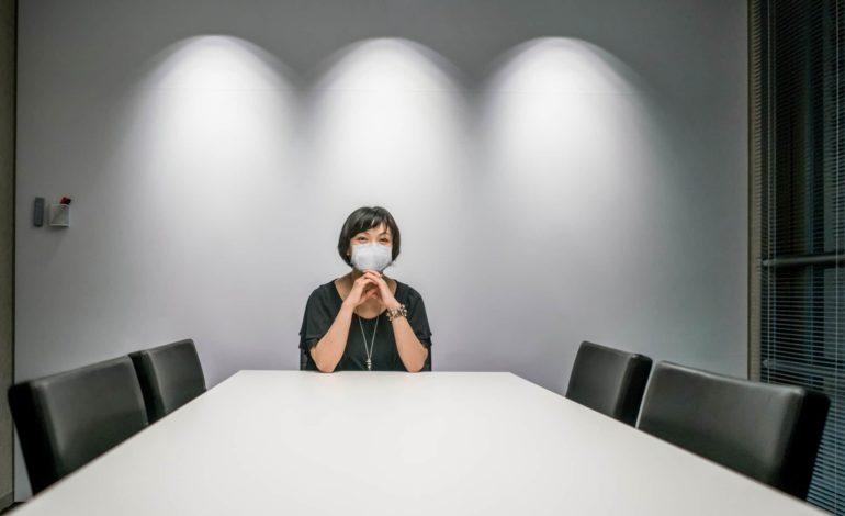 Vereins- und Gesellschaftsrecht: Eine Frau mit Mund-Nasen-Maske sitzt alleine an einem großen Tisch in einem Sitzungssaal. Die anderen vier Stühle sind leer.