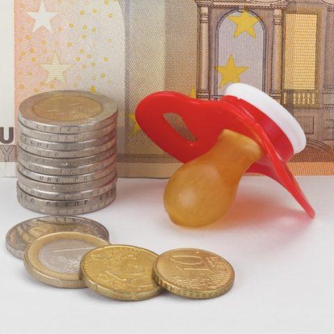 Im Hintergrund ist ein 50 Euro Schein und im Vordergrund liegt Kleingeld. Münzen bilden einen Stapel, daneben liegt ein roter Schnuller. Es geht um Unterhalt für Kinder.