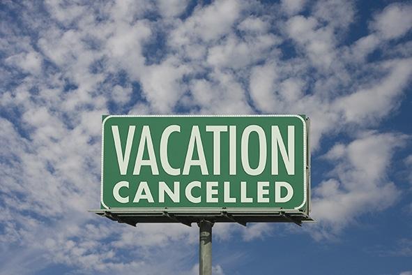 """Grünes Schild auf dem """"Vacation cancelled"""" steht. Gemeint ist Reiserücktritt aufgrund von Corona."""