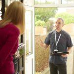 Haustürgeschäfte: Eine Frau macht einem Mann die Haustüre auf. Er hält ein Klemmbrett in der Hand und möchte der Frau etwas verkaufen.