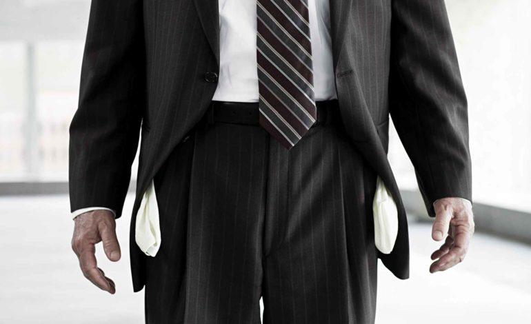 Corona Insolvenz: Mann im Anzug mit herausgezogenen Hosentaschen