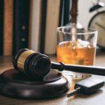 Alkoholglas mit Autoschlüssel und Richterhammer