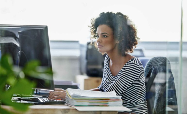 Junge Frau sitzt am Schreibtisch vor Ihrem Computer.