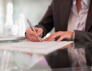 Eine Frau unterzeichnet einen Vertrag mit einem Kugelschreiber