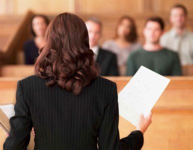 Im Gerichtssaal sitzen Zuschauer und eine Vorsitzende.