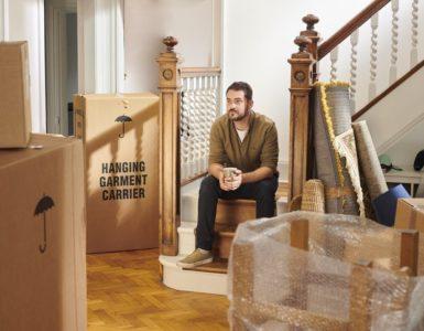 Ein Mann sitzt in seiner Wohnung auf einer Treppe. Um ihn herum stehen verpackte Möbel und Kartons. Er wirkt bedrückt. Kündigung durch Vermieter.