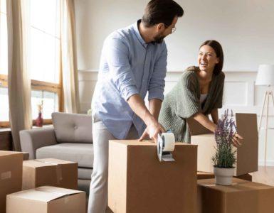 Ein Mann und eine Frau packen Kartons für den Umzug.