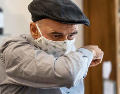 Älterer Mann mit Maske niest in seine Armbeuge.