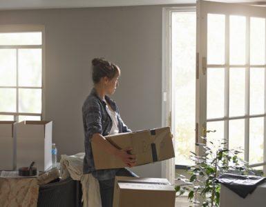 Räumungsklage: Eine Frau trägt Umzugskartons ins Freie. Die Tür steht offen und viele gepackte Kartons stehen bereit. Die Frau sieht traurig aus.
