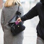 Ein Mann mit Kapuze über dem Gesicht stiehlt einer vorbeigehenden Dame das Portmonnaie aus ihrer Tasche.