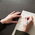 Frau unterschreibt Vertrag über die Erbschaftsteuer