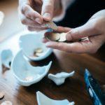 Leistungsverweigerungsrecht: Auf einem Tisch ist ein kaputtes Sparschwein. Es liegen ein paar Euros und ein Hammer auf dem Tisch. Zwei Hände sind zu sehen, die Geldstücke zählen.