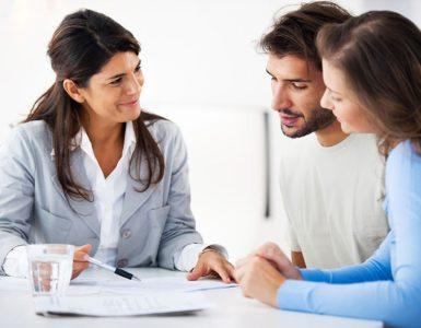 Rechtsschutzversicherung: Eine Frau erklärt einem Paar etwas. Sie sitzen an einem Tisch und haben Unterlagen vor sich liegen.