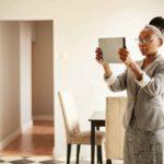Eine Vermieterin hält ihr Tablet vor sich in den Händen um Bilder von der Wohnung zu machen.